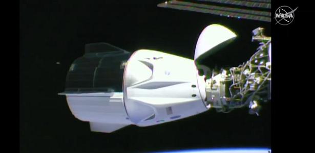 Cápsula do dragão da tripulação com astronautas da NASA chega à ISS
