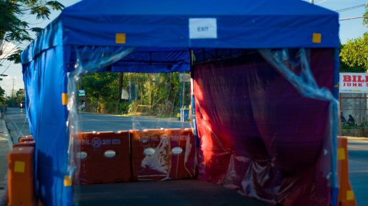Exemplo de uma barraca de desinfecção montada em uma avenida principal de uma província nas Filipinas - Sergio Pontillas / Getty Images