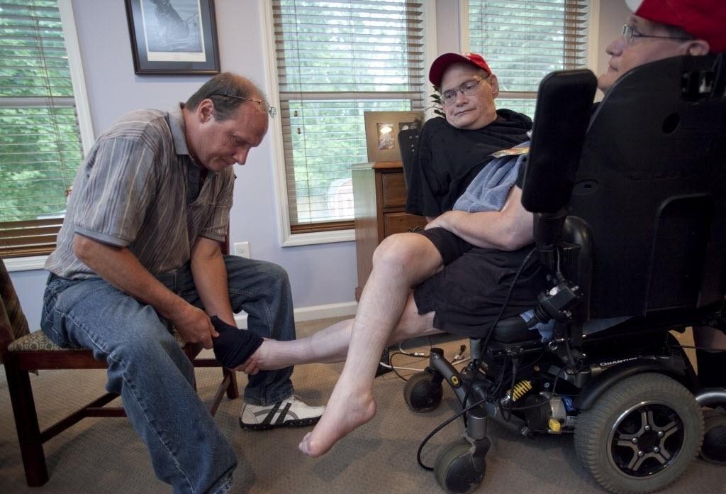 3 de julho de 2014 - Jim Galyon (à esquerda) ajuda seus irmãos Donnie e Ronnie a tirar as meias em sua casa em Beavercreek, Ohio, EUA. Irmãos nascidos em 28 de outubro de 1951 estão perto de serem reconhecidos como os irmãos siameses mais longos - Daily News, Drew Simon / AP
