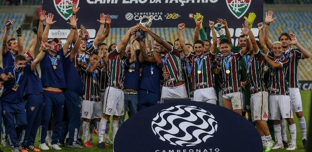 Os jogadores ligam e os médicos do clube levantam o troféu para o pódio
